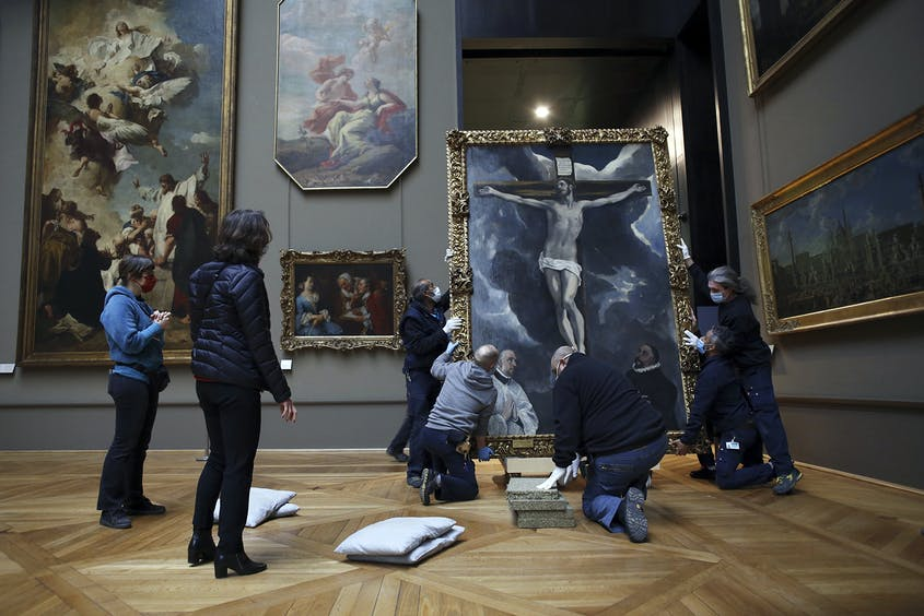 """Workers at the Louvre handle a painting called """"Christ on the Cross Adored by Two Donors"""" by Spanish painter El Greco, as it returns from an exhibition at the Art Institute of Chicago."""